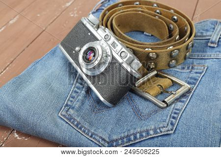 Clothes, Shoes And Accessories - Closeup Top View Retro Photo Camera, Leather Belt And Blue Jeans On