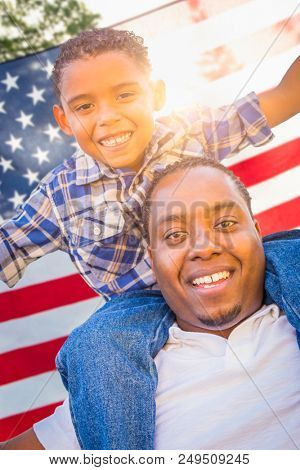 African American Father and Mixed Race Son Piggy Back with American Flag