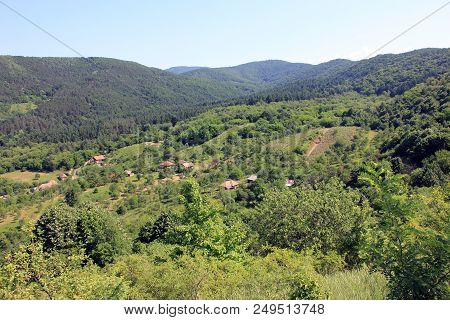Panorama Of A Green Hill, Houses Scattered On The Hill Slope. Preserved Nature Environment.