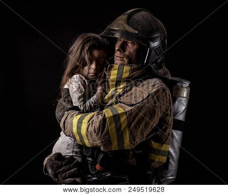 Dirty Firefighter In Uniform Holding Little Saved Girl Standing On Black Background.