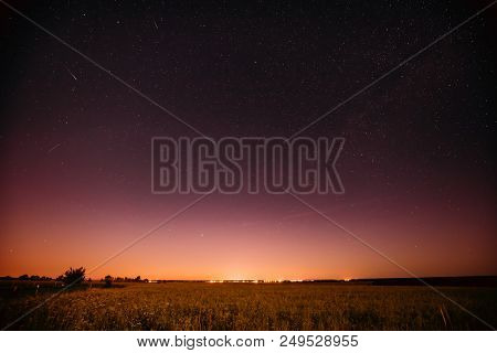 Natural Night Starry Sky Above Summer Field Meadow. Glowing Stars, Meteorite Trail And Sunset Sunris