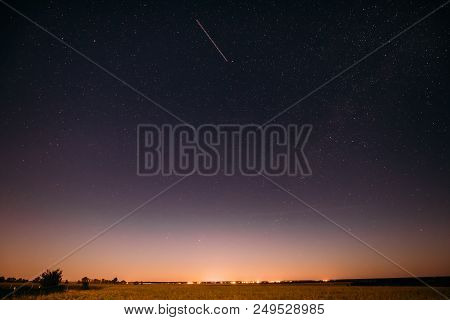 Natural Night Starry Sky Above Summer Field Meadow. Glowing Stars, Aircraft Light Trail And Sunset S