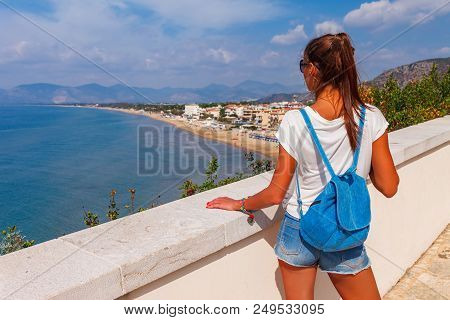 Young Tourist Woman On The Beach And Sea Landscape With Sperlonga, Lazio, Italy. Scenic Resort Town