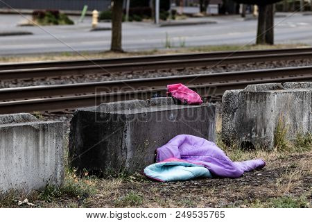 Homeless Child's Sleeping Bag Next To A Railroad Track Concrete Block
