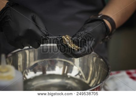 Man's Hands In Black Gloves With Knife And Shucking Fresh Oysters On A Seafood Market. Gastronomic D