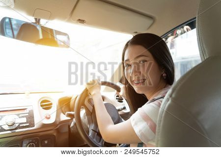 Young Asian Woman Driving Car Keeps Wheel Turning Around Smiling Looking At Passengers In Back Seat