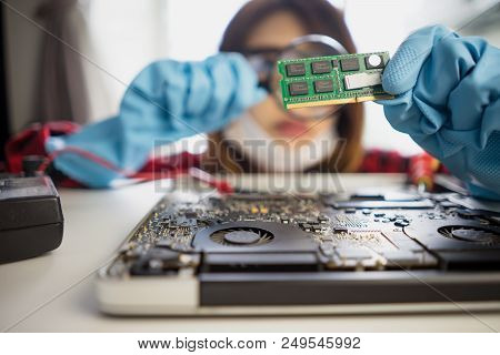 Engineer Repairs Laptop Support Fixing Notebook Computer. It Woman Using Magnifying Glass Installs E
