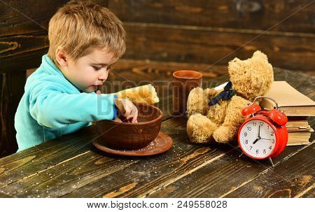 Kid Eat Food At Wooden Table. Kid Enjoy Meal With Toy Friend. Kid Menu. Little Kid Eating. You Are W