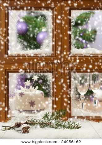 Falling winter snow onto pine cones and branch against a festive Christmas window, focus on pine cones and branch in front of window