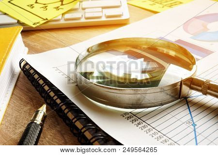 Business Assessment And Audit. Magnifying Glass On A Financial Report.