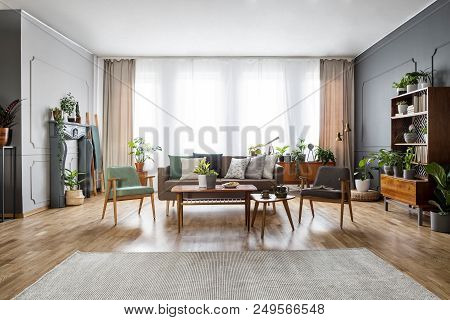 Real Photo Of A Spacious, Vintage Living Room Interior With A Sofa Between Two Chairs And Behind A T
