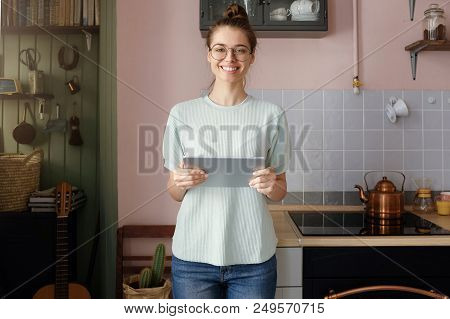 Indoor Picture Of Young Good-looking Caucasian Girl Standing In Her Flat Holding Tablet Looking Stra