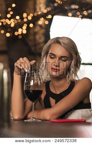 Thinking Intently. Gorgeous Blonde Woman Running Her Finger Along The Rim Of A Wine Glass And Contem