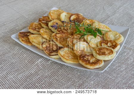 Plate Full Of Pancakes With Branches Of Mint Standing On A Table Covered With Textile Table-cloth