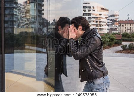 Side View Of Man In Leather Jacket And Jeans Looking Inside Of Window Leaning To Glass While Standin