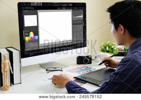 Asian Male Designer Using Graphics Tablet While Working With Computer At Studio Or Office.