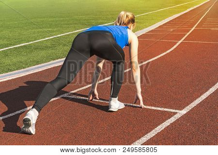 Teen Girl In The Starting Blocks At A Track Meet. Sports Start. Girl In Pose On The Starting Line Of