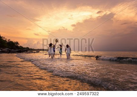 Summer Of Happy Girls Running Together On Sunset Sea Beach. Holiday Concept. Cinema Film Tone With G