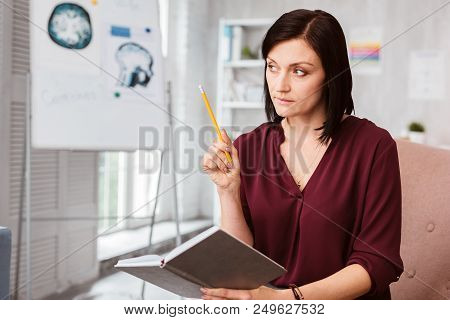Careful Consideration. Calm Attentive Neurologist Thoughtfully Holding A Pencil And A Notebook While