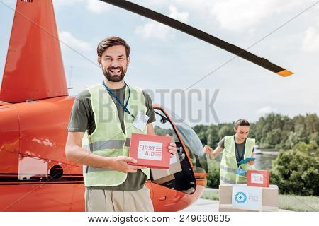 Volunteer Service. Jovial Male Volunteer Holding Kit And Grinning To Camera