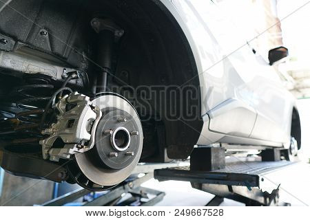 Close Up Of Brake Disc Of The Vehicle For Repair.automobile Mechanic In Process Of New Tire Replacem