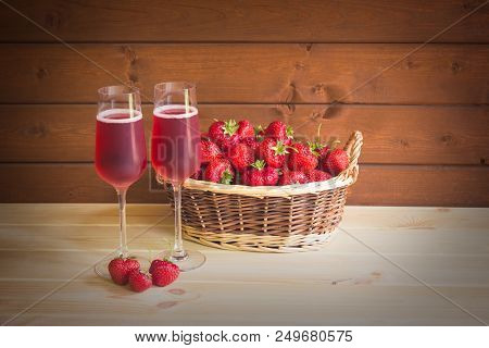 Two Glasses Of Rose Champagne And Fresh Strawberry In Wicker Basket