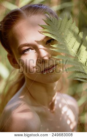 Portrait Of A Red-haired Girl With Long Hair. The Hair Gathered In A Ponytail. Near The Face Fern. A
