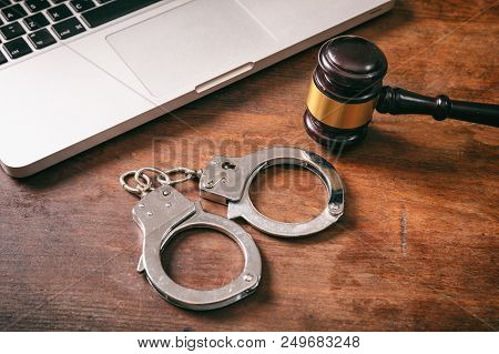 Cybercrime And Law Concept. Handcuffs And A Judge Gavel And A Computer On A Wooden Background.