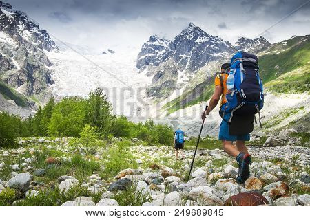 Climbers With Hiking Backpacks Go To The Mountain. Hikers In Mountains. Tourists Hike On Rocky Mount
