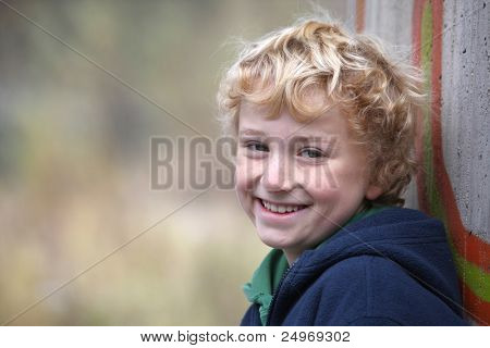 portrait of a cute smiling young boy leaning on a concrete wall