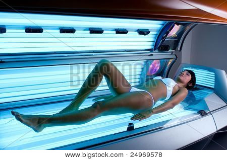 Young beautiful latin lady lying on a tanning bed at health spa