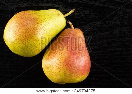 Group of two whole fresh red pear forelle variety flatlay on black wood poster
