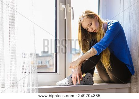 People and solitude concept. Alone sad young woman long hair teen girl sitting on window sill lost in thought, urban city in the background poster