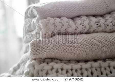 Background with warm sweaters. Pile of knitted clothes in warm shades, warm background, knitwear, space for text, Autumn winter concept. Copy Space. poster