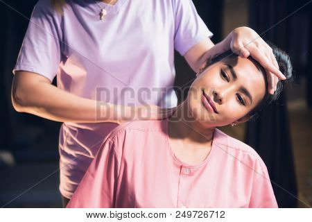 Portrait Of Relaxed Asian Beautiful Woman Massaging Neck And Shoulder By Professional Massager In Sp