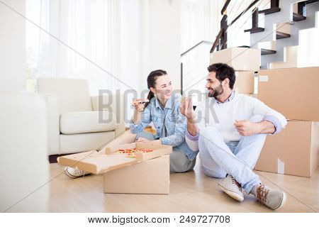 Young man and woman in casualwear sitting on the floor of their new house and eating pizza by talk