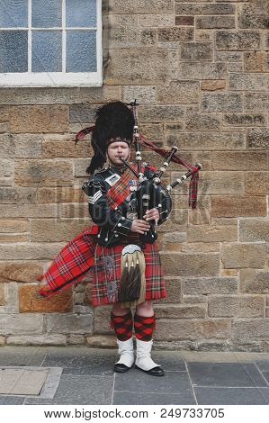 Edinburgh, Scotland - April 2018: A Scottish Piper Man Dressing In Scottish Traditional Tartan Kilt