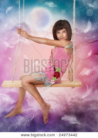 Little girl sitting on the swing