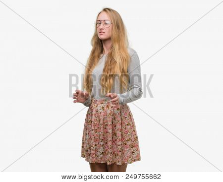 Blonde teenager woman wearing flowers skirt disgusted expression, displeased and fearful doing disgust face because aversion reaction. With hands raised. Annoying concept. poster