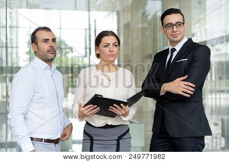 Ambitious Business Team Of Three Looking Forward. Group Of Specialists With Folder Of Documents. Tea
