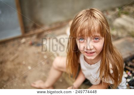 Portrait Of Tense Vulnerable Blond Little Girl With Matted Hair In Dirty Alley, Shallow Depth Of Fie