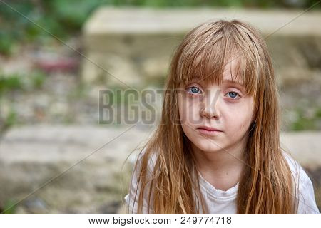 Portrait Of Sad Vulnerable Blond Little Girl With Matted Hair In Dirty Alley, Shallow Depth Of Field