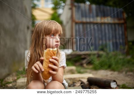Portrait Of Poor Hungry Homeless Girl Eating A Piece Of Bread In The Dirty Alley, Selective Focus. P