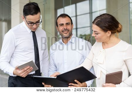 Middle-aged Caucasian Businessman Meeting With Coworkers. Smiling Business Executive Discussing Cont