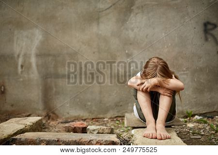 Street Photo Of Depressed Blond Girl Orphan With Long Matted Hair With Holen Knees Under The Dirty C
