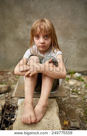 Street photo of blond girl orphan with long matted hair in the dirty alley, shallow depth of field, selective focus, vertical. Poverty and poorness on the children face. Tense little girl. Social inequality. Abandon generation. Poverty concept. poster
