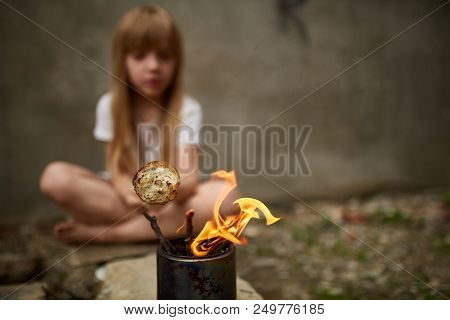 Homeless Girl Frying Bread In The Fire From The Can Under The Street Wall In The Dirty Alley, Shallo