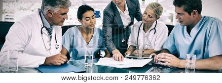 Team of doctors and businesswoman having a meeting in medical office