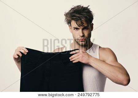 Athlete With Messy Hair And Trousers In Hands. Guy With Concentrated Face Isolated On White Backgrou