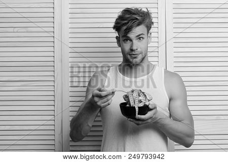 Athlete With Messy Hair And Unshaved Face. Guy In Sleeveless Shirt Eating Measuring Tape. Man With S